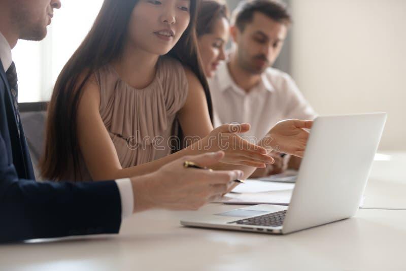 Discusión del negocio, empleado asiático que habla con el colega que señala en el ordenador portátil fotografía de archivo libre de regalías