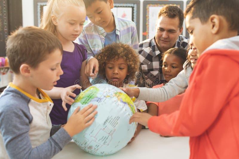 discusing在地球地球的教师在教室在学校 免版税库存照片