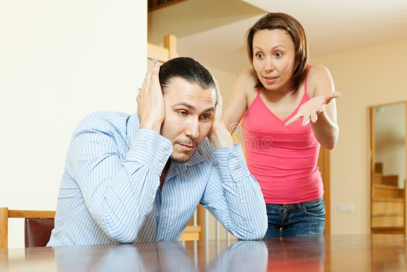 Discussão da família. Homem cansado que escuta sua esposa irritada foto de stock