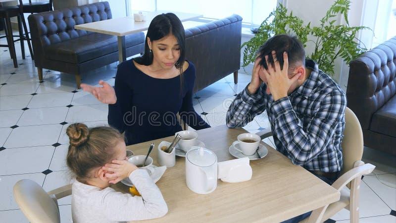 Discussão da família no café A mãe é xingamento muito nervoso na filha e no marido fotos de stock