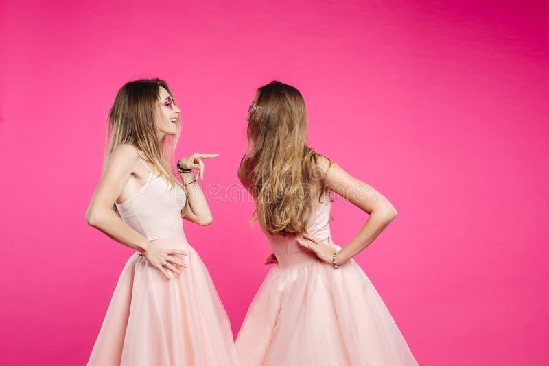 Discussão de duas irmãs em vestidos cor-de-rosa foto de stock
