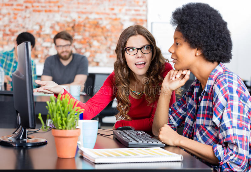 Discussão de fala da mulher de dois colegas sentando a mesa de escritório fotografia de stock royalty free