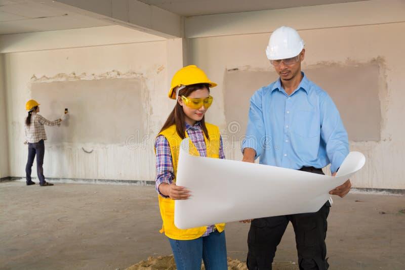A discussão do arquiteto e do construtor no projeto imobiliário inspeciona imagens de stock royalty free