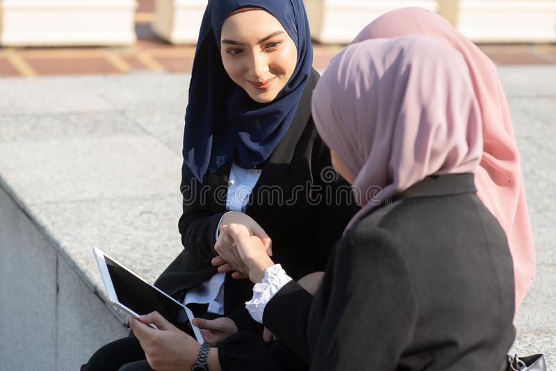 Discussão e aperto de mão muçulmanos das mulheres de negócio foto de stock