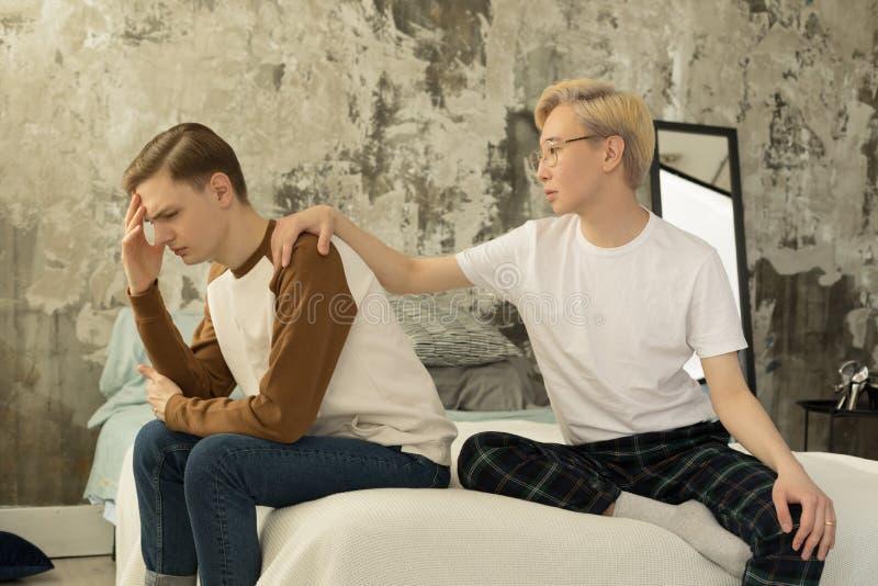 Discussões alegres novas dos pares na cama Homem europeu deprimido que senta-se na borda da cama imagens de stock