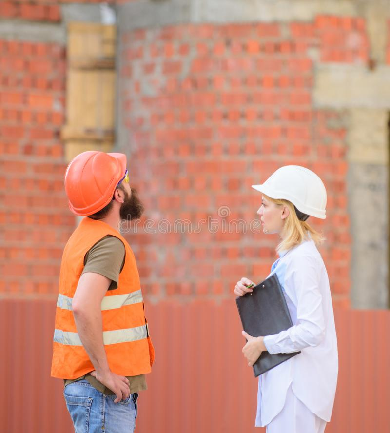 Discuss progress plan. Construction industry concept. Relationships construction client and participant building. Industry. Woman engineer and bearded brutal stock photo