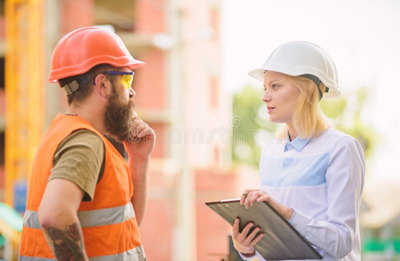 Discuss progress project. Construction project inspecting. Safety inspector concept. Woman inspector and bearded brutal royalty free stock image