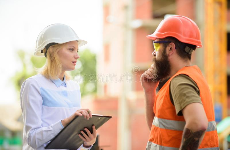 Discuss progress project. Construction project inspecting. Safety inspector concept. Woman inspector and bearded brutal stock photo