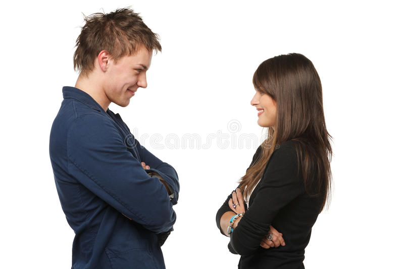 Discussing. Side view of a beautiful young couple standing face to face and looking at each other, isolated on white background stock image