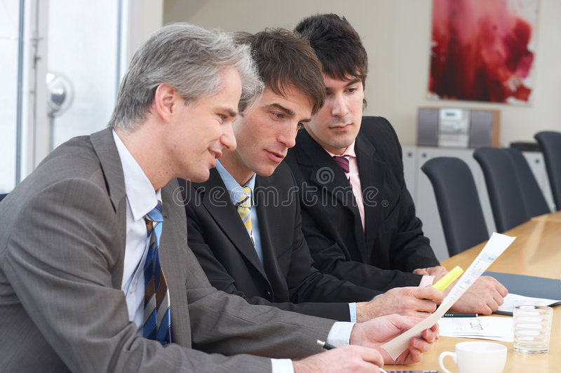 Discussing. Three businessmen are discussing something on a meeting