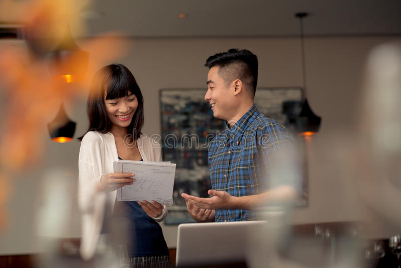 Discussing business idea. Cheerful Vietnamese couple discussing business idea stock image