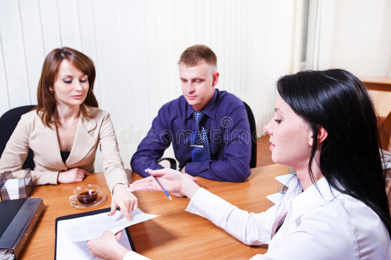Discussing contract. Customers discussing contract issues with their consultant royalty free stock photography
