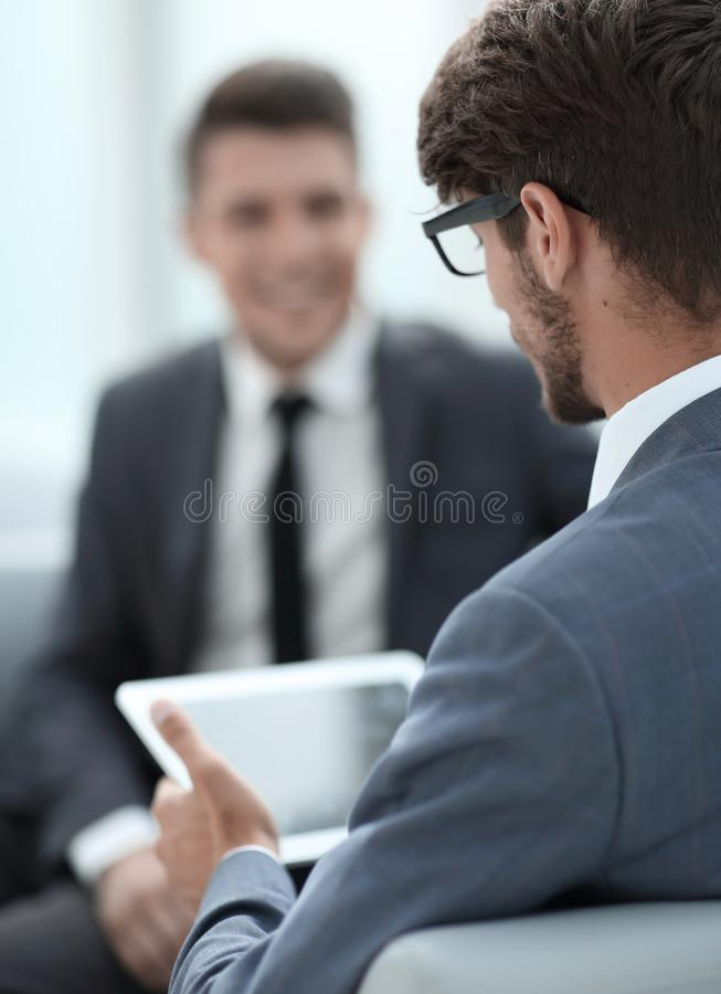 Two young businessmen discuss ideas with a tablet stock images