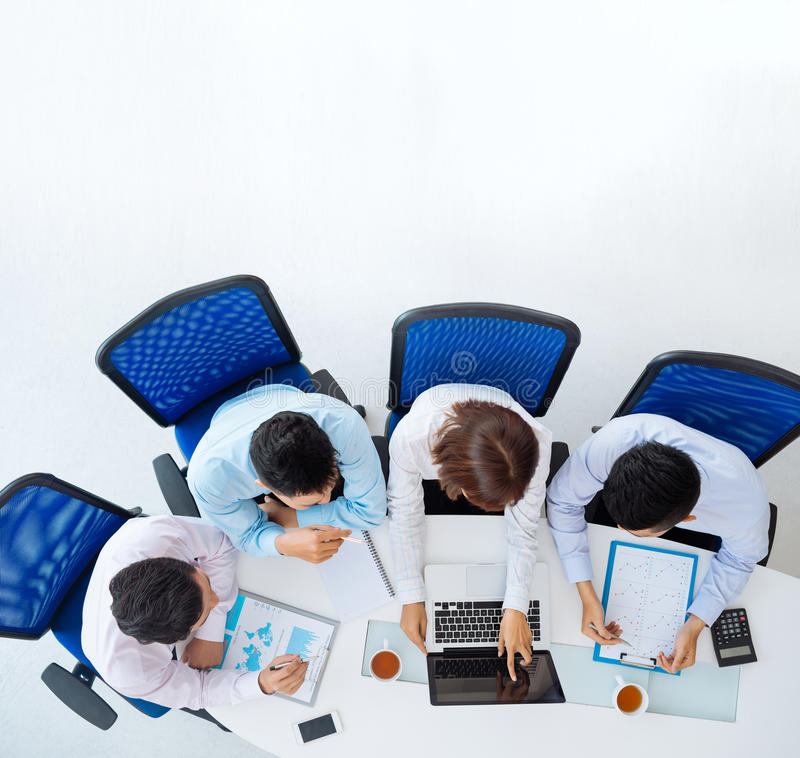 Discussing financial reports. Business team discussion financial reports, view from above stock photo