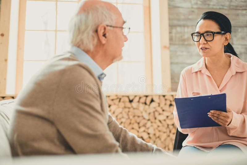 Confident dark-haired woman in clear glasses talking to old man. Discussing his staying. Confident dark-haired women in clear glasses talking to old men and stock images