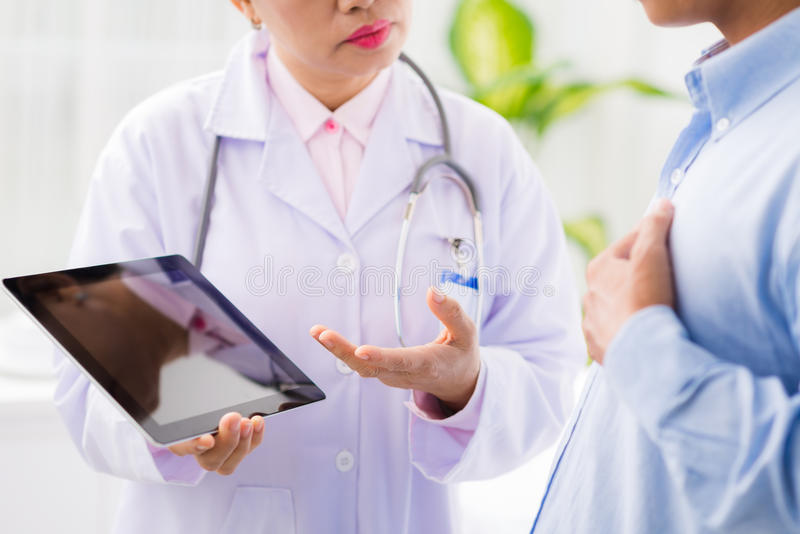 Discussing medical records. Doctor discussing medical records on the digital tablet with patient royalty free stock photography