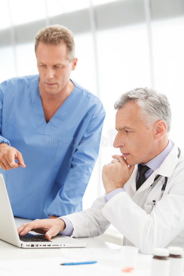 Discussing medical reports. Mature doctor using computer and dis royalty free stock images