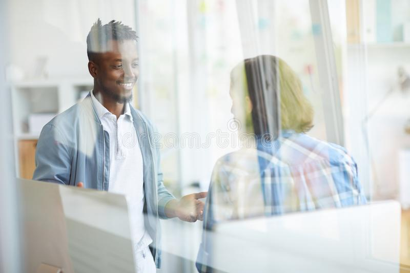 Discussing new strategy. Two young specialists having discussion of new working ideas and strategies in office royalty free stock photos