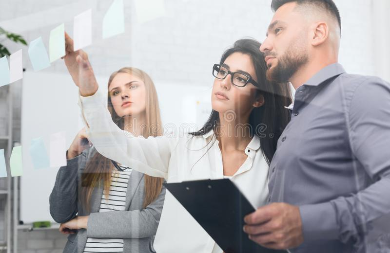 Discussing plans. Business people sticking adhesive notes. On glass board in office royalty free stock image