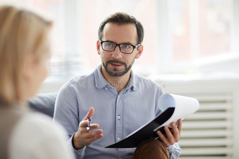 Discussing problem of patient. Young confident counselor with pen and document explaining something to his patient during conversation stock photo