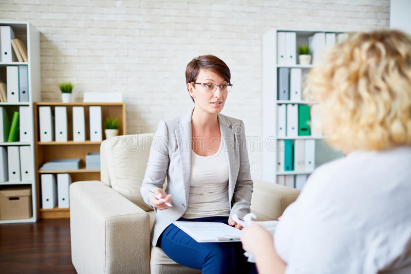 Discussing problem. Young specialist consulting women with overweight stock image