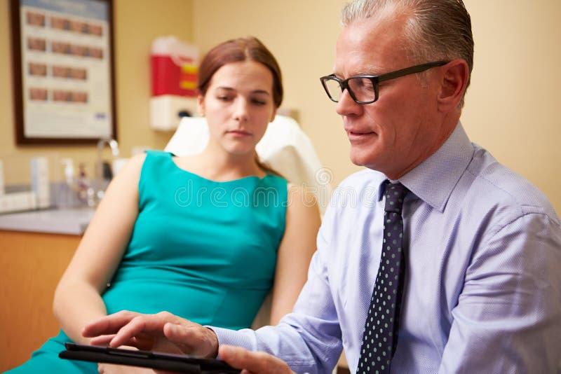 Discussing Procedure With för kosmetisk kirurg klient i regeringsställning arkivfoto