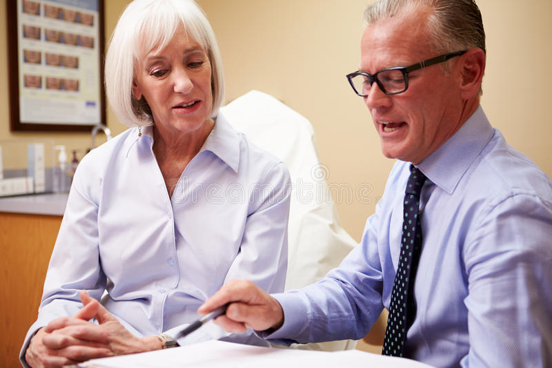 Discussing Proceedure With för kosmetisk kirurg klient i regeringsställning royaltyfri bild