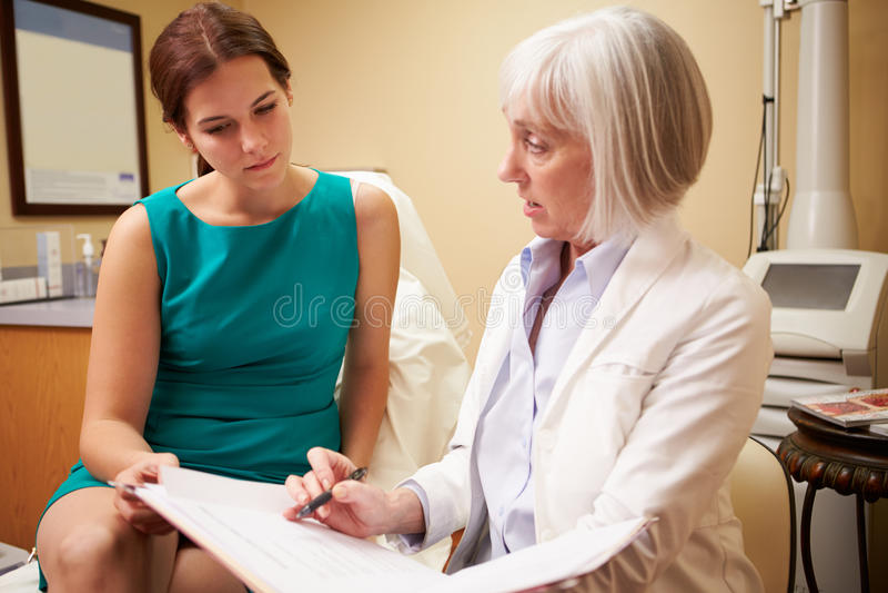Discussing Proceedure With för kosmetisk kirurg klient i regeringsställning arkivfoto
