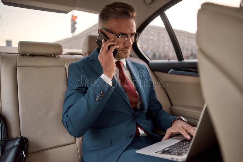 Discussing project details. Confident and stylish mature businessman in full suit working on his laptop and talking on stock photos