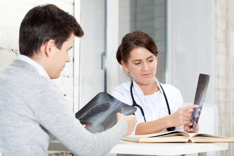 Discussing X-Ray results. Patient and doctor discussing X-Ray results royalty free stock image