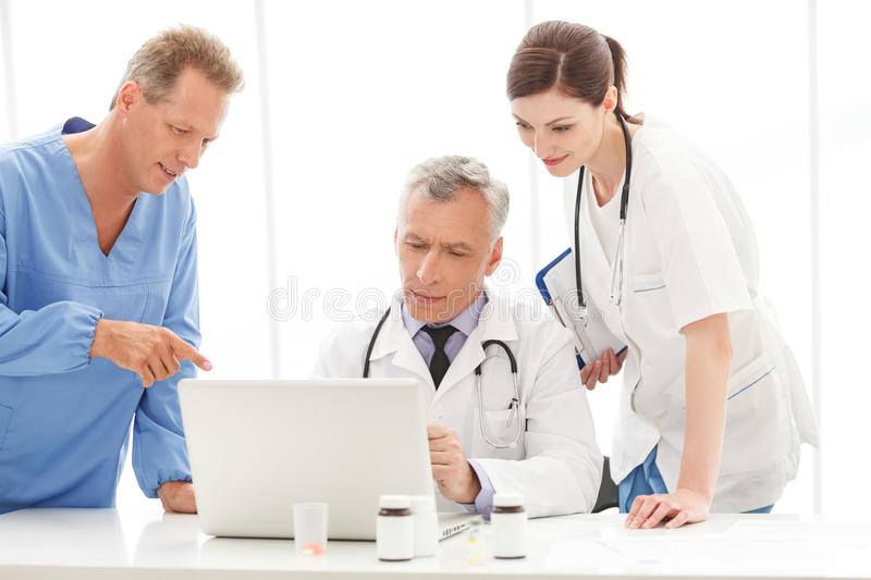 Discussing the report. Medical doctors team discussing something. On the computer royalty free stock photos