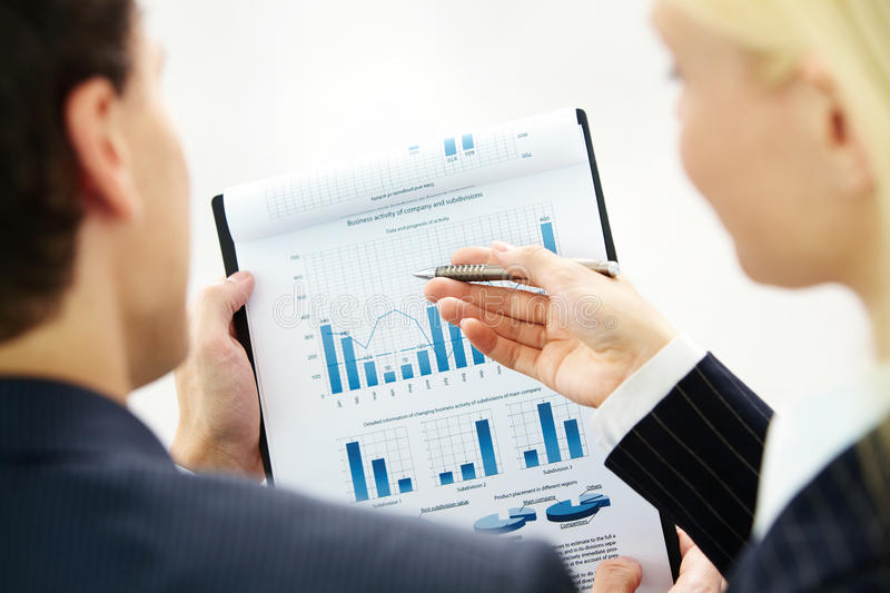 Discussing resources. Image of paper being discussed by two business partners stock image