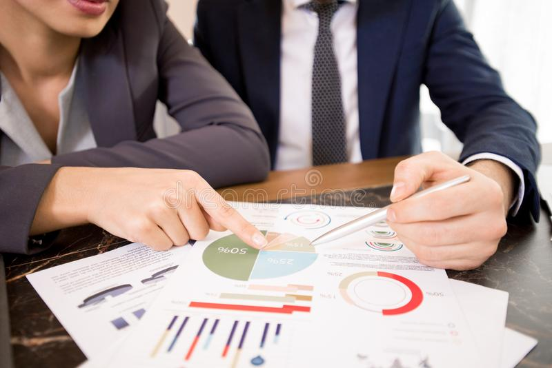 Discussing results of business research. Close-up of unrecognizable business analyst viewing survey report and discussing results of research at table, women stock image