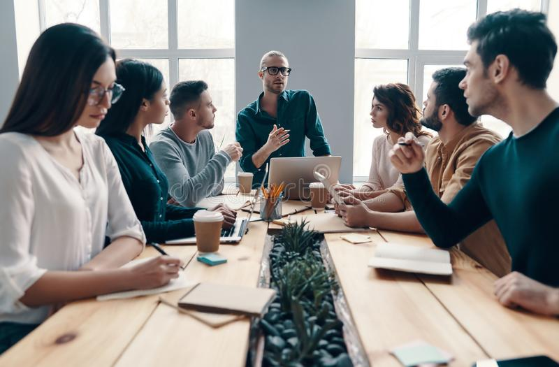 Discussing risky ideas. Group of young modern people in smart casual wear discussing something while working in the creative office royalty free stock photos