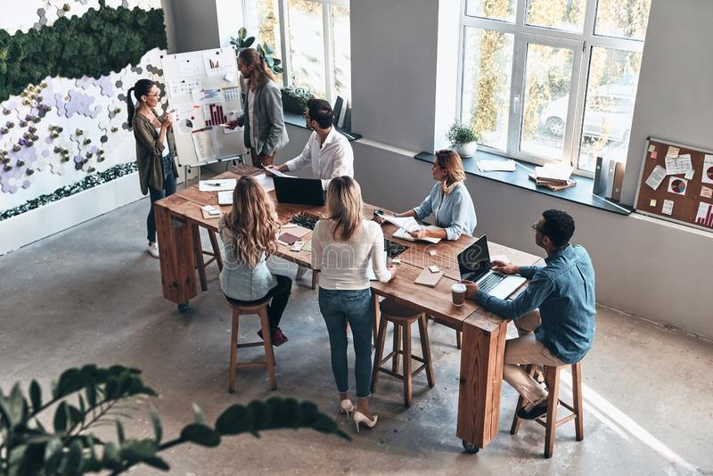 Discussing risky ideas. Top view of two modern young colleagues conducting a business presentation while standing in the board room stock image