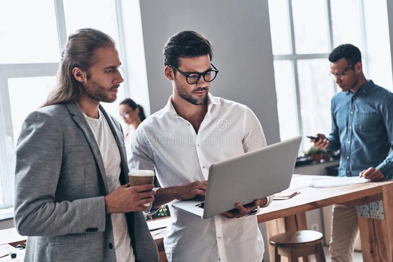Discussing risky ideas. Two young modern men in smart casual wear using laptop while working time in the creative office royalty free stock photography
