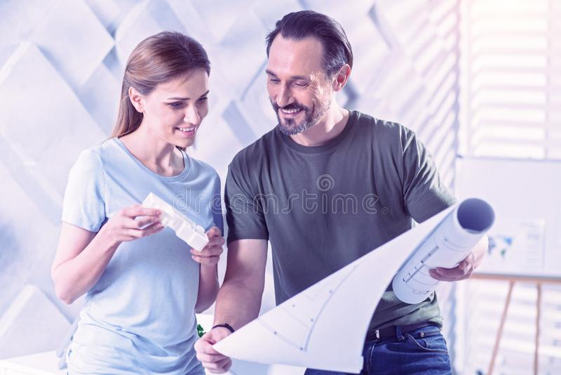Friendly architects smiling while looking at the new blueprint royalty free stock images