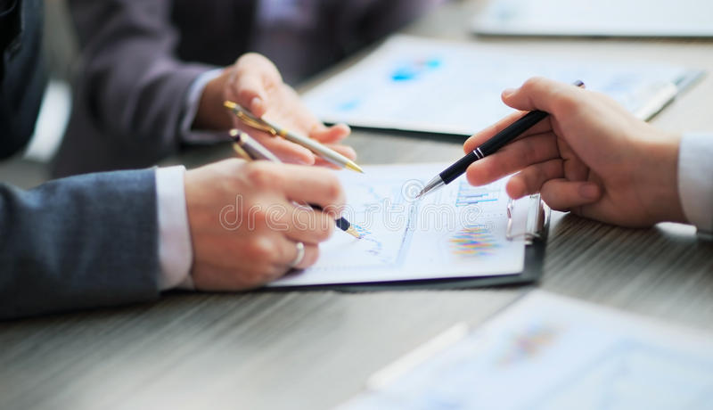 Discussing the scheme. Side view of business people, pointing handles on the chart together. Sitting at the table royalty free stock photo