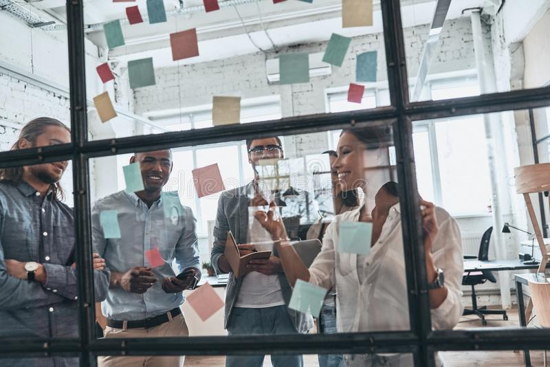 Discussing strategy. Group of young modern people in smart casual wear using adhesive notes while standing behind the glass wall stock photography