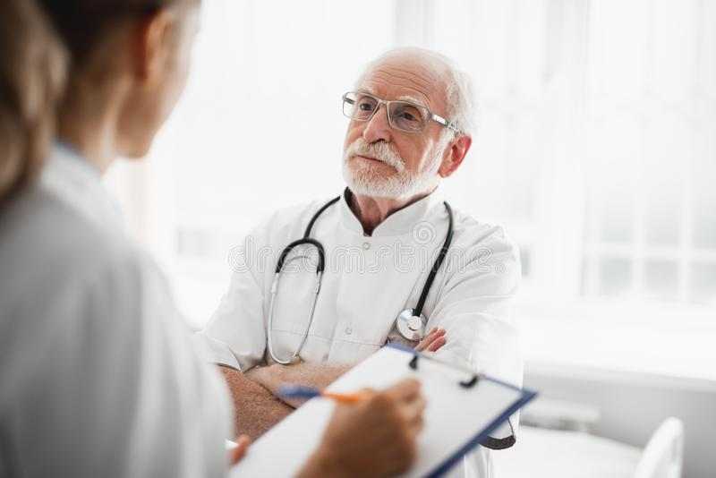 Old doctor looking at nurse while standing in hospital room stock photography