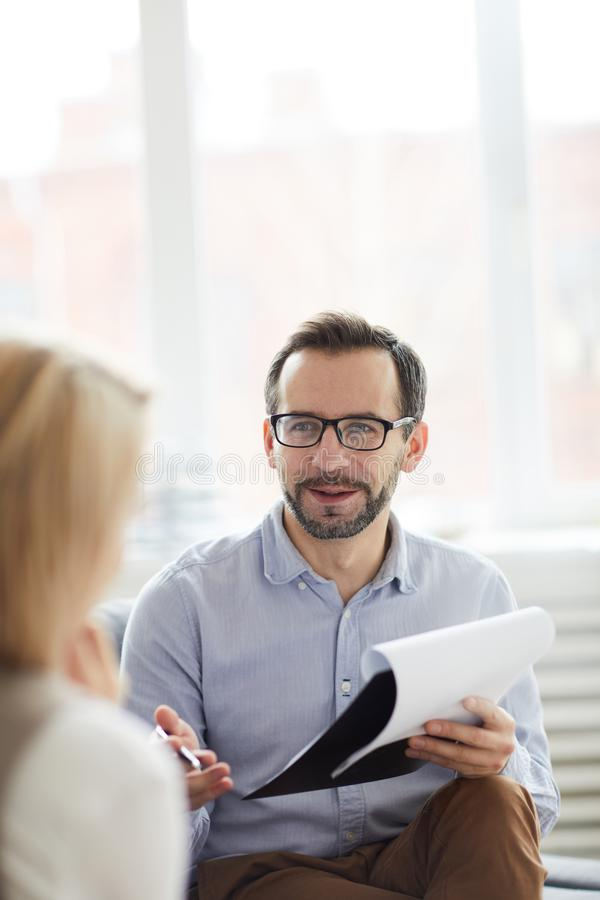 Discussing ways of solving problem. Confident counselor with document giving advice to his patient while discussing ways of solving her problem royalty free stock photos