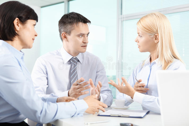 Discussion. Three business partners sitting in office and interacting at meeting royalty free stock photo