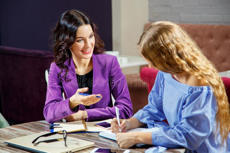 Discussion business. Two young women in casual clothing talking and gesturing, sitting at the table.  royalty free stock photography
