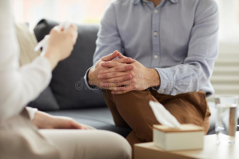 Discussion on couch. Crossed hands on knees of contemporary psychologist during discussion of patient problem on couch royalty free stock photo