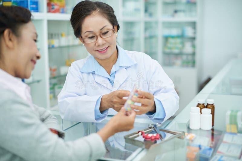 Discussion de la médecine avec le travailleur de pharmacie photos libres de droits