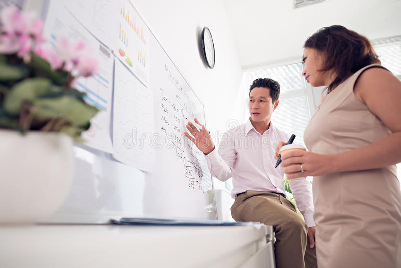 Discussion. Portrait of confident business partners discussing ideas on whiteboard in office stock photo