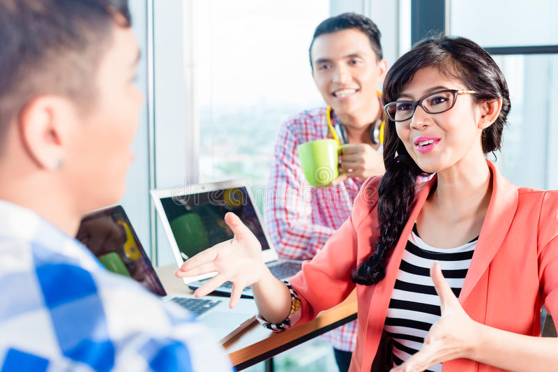 Discussione creativa asiatica dei lavoratori dell'agenzia immagini stock