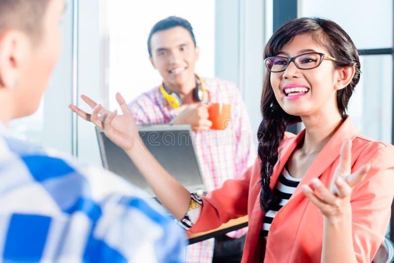 Discussione creativa asiatica dei lavoratori dell'agenzia immagine stock libera da diritti