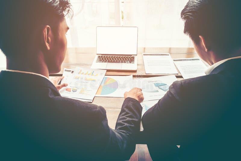 Discussione dell'uomo di affari circa il grafico di rapporto di vendita con il computer portatile bianco dello schermo sulla tavo immagine stock