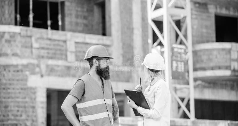 Discuta el proyecto del progreso Concepto del inspector de la seguridad Inspector y constructor brutal barbudo discutir progreso  imágenes de archivo libres de regalías